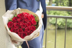 バラの花束を持つスーツ姿の男性